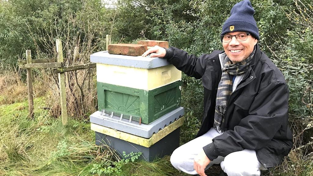 Biodlaren Lekbir Belmhemdi sitter bredvid en av sina bikupor.