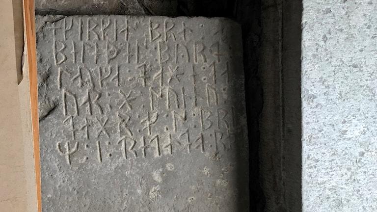 Runor på sten som hittats under golvet i Hejde kyrka.