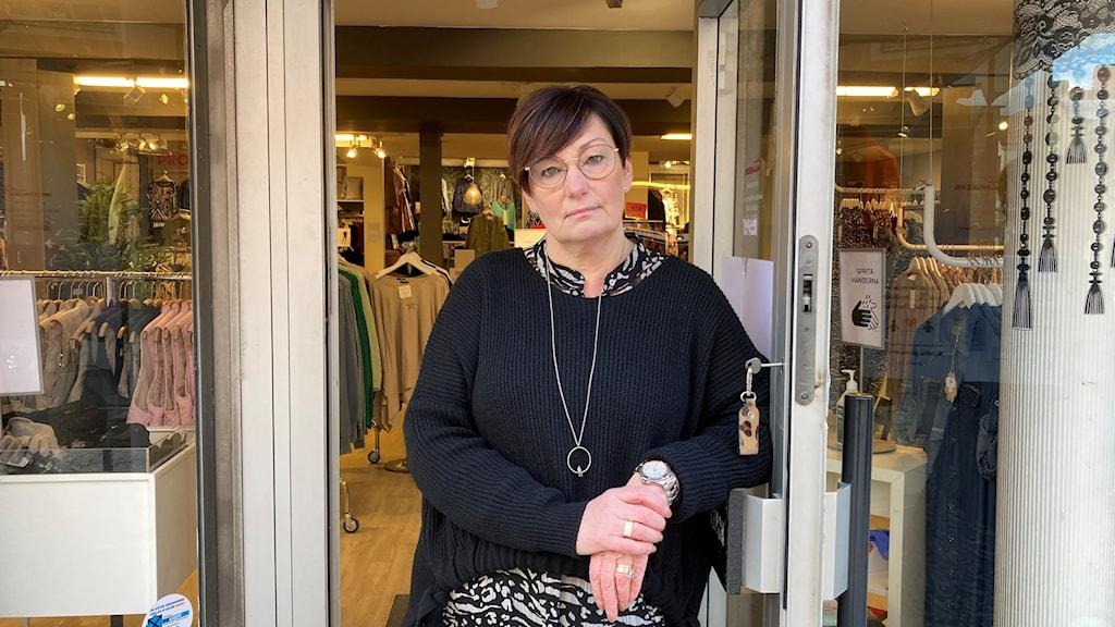 En kvinna står i entrén till en butik