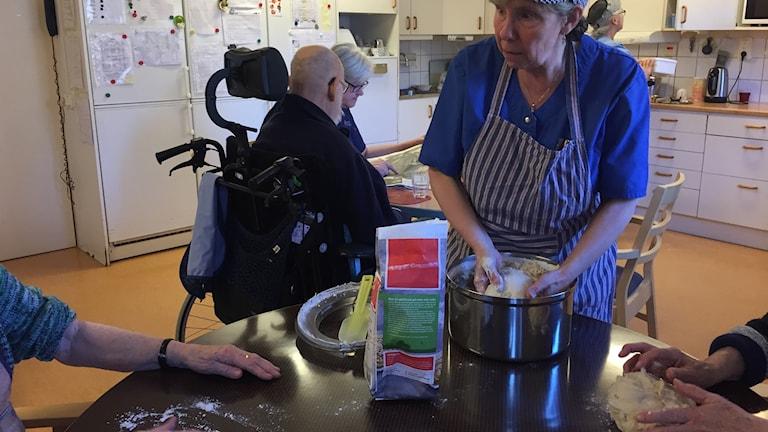 Bitte Ispegren får hjälp av de boende på Iliansgården att baka bullarna till fikat.