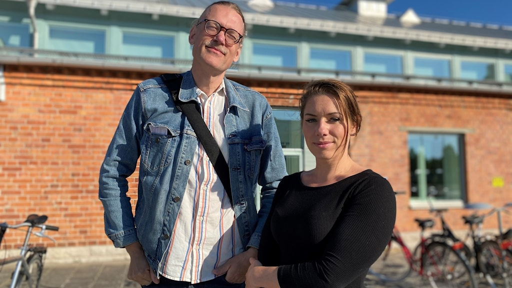 Två personer står framför ett tegelhus.