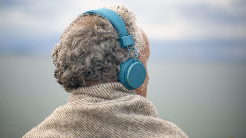 En person med kort, grått hår med hörlurar på sig blickar ut över vatten.