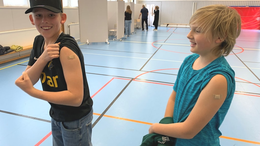 Två tolvåriga killar står i en gympasal och visar upp sina plåster efter covid-19-vaccinsprutan.