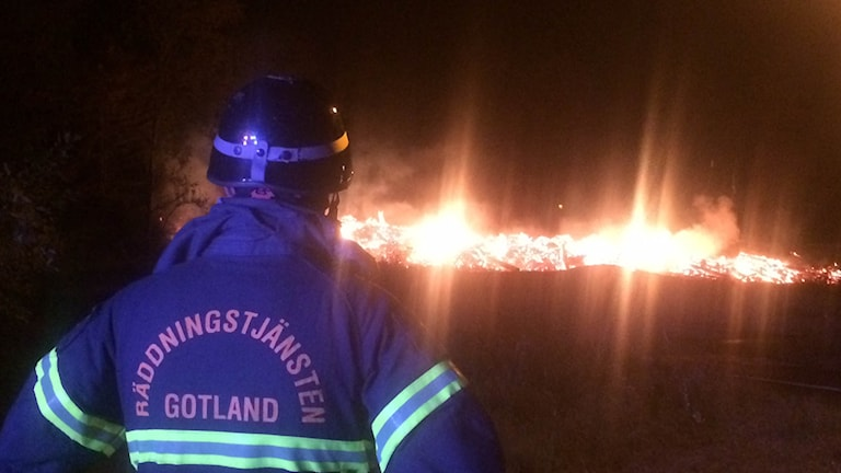 Brandman framför glödande hög nattbild.