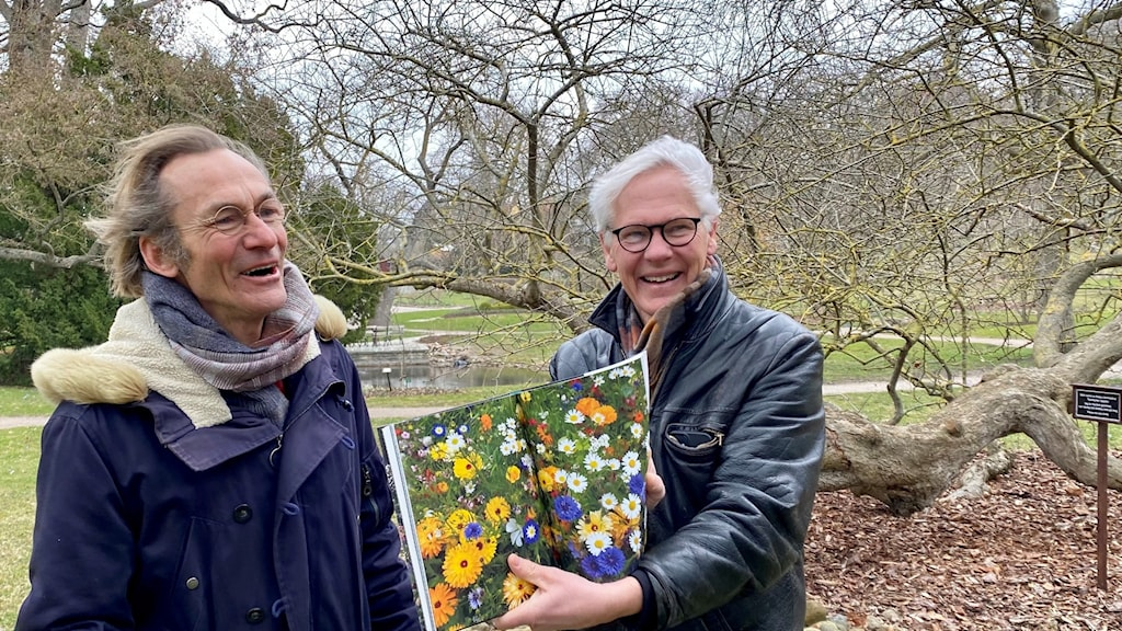Två män står i en park. I handen håller den ena mannen ett bok. Han visar upp ett bokuppslag som är fyllt av blommor.