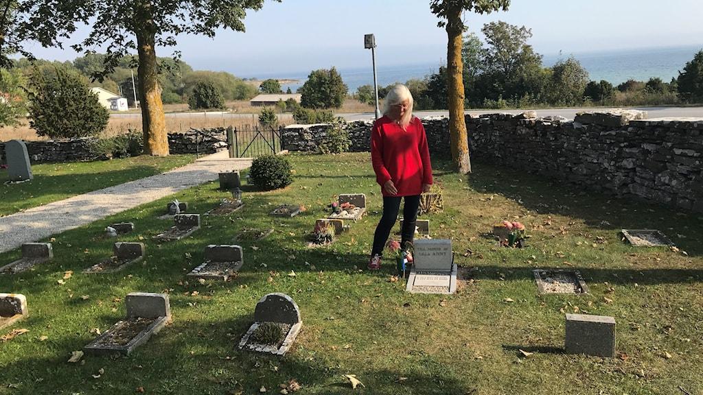 Kerstin Blomberg vid lilla Annys grav, Fårö kyrkogård.