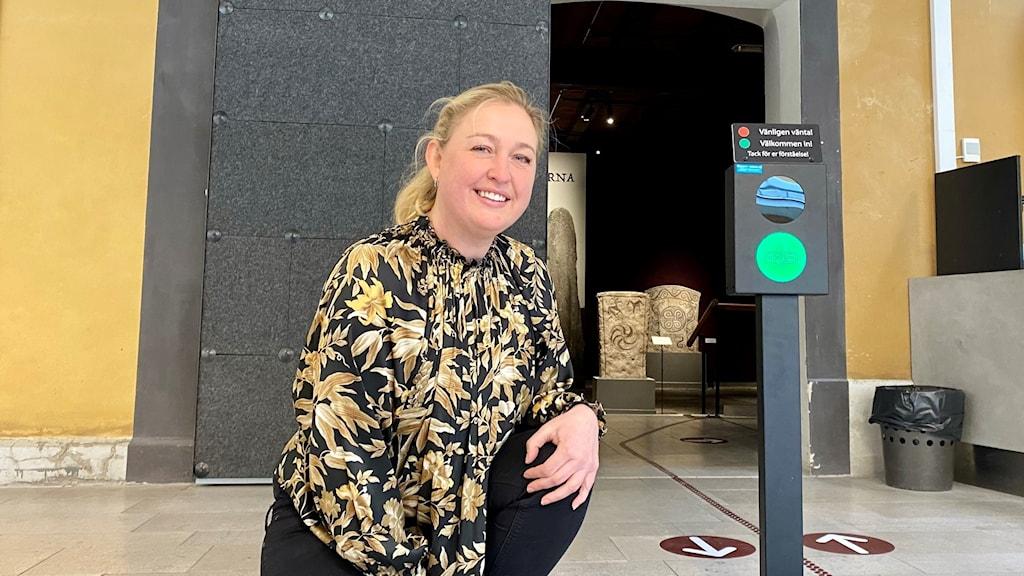 En kvinna vid entrén till museet försedd med en grön lampa.