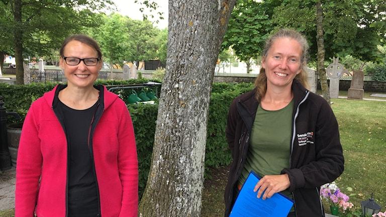Två kvinnor intill ett almträd
