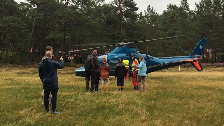 Personer vid helikopter.