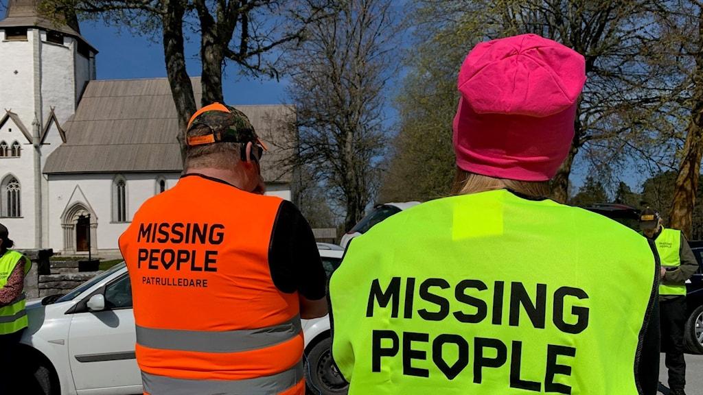 Ryggtavlorna på två män i gul respektive rosa reflexväst. I bakgrunden syns en kyrka.