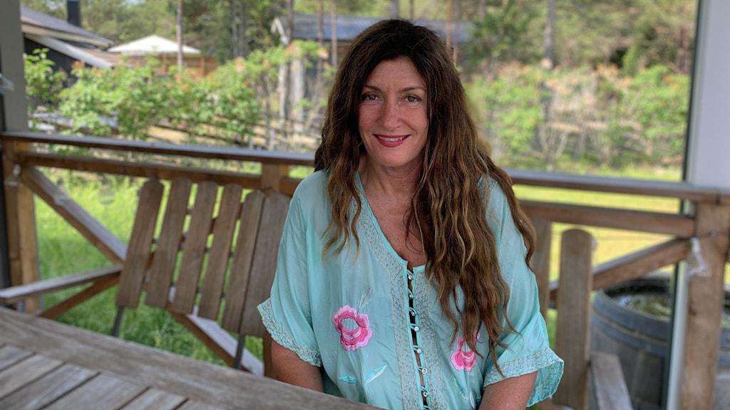 Mari Jungstedt sitter utomhus i skuggan.