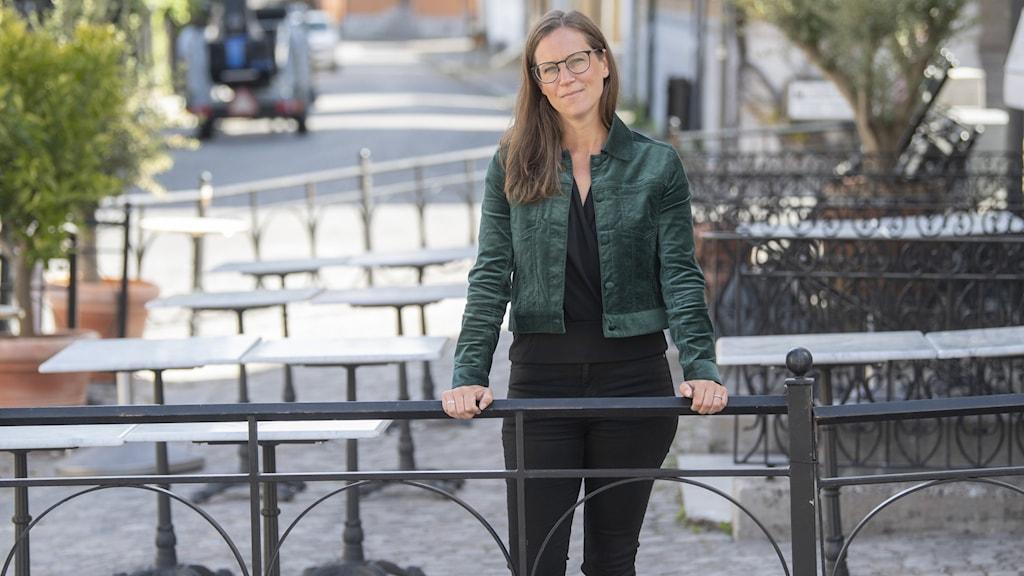 Frida Ganshed, vd för Gotlands förenade besöksnäring, står vid en uteservering och håller i ett räcke och ser in i kameran.