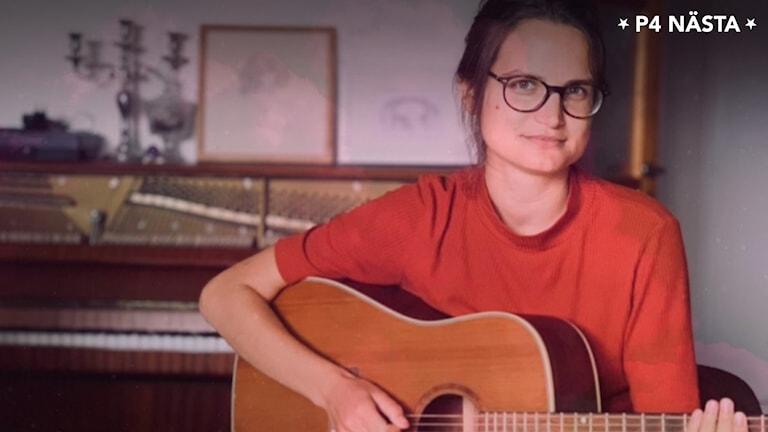 En kvinna med en gitarr.