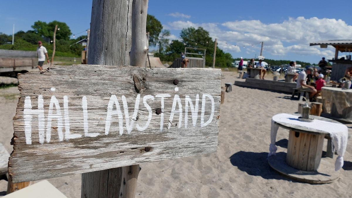 Bord på strandcafé och skylt med budskapet att hålla avstånd