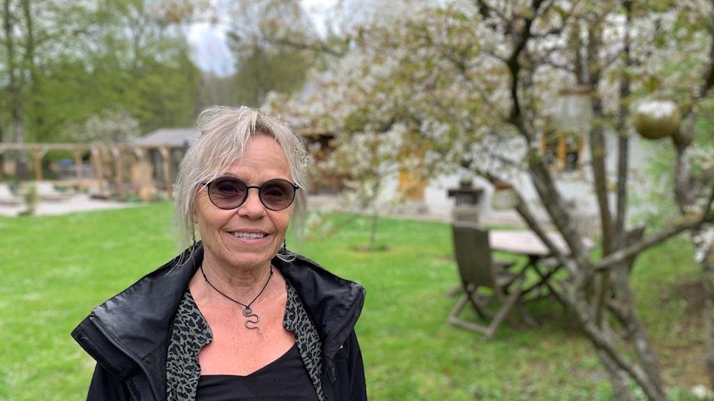 Porträttbild på kvinna i trädgård och som bär solglasögon.