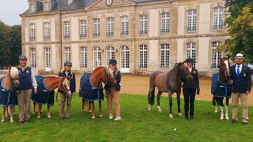 Fem personer och fem hästar står framför ett stort stenhus.