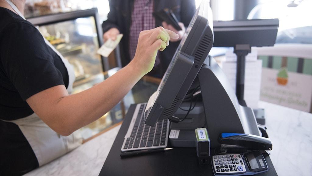 En man betalar med kontanter i butik.