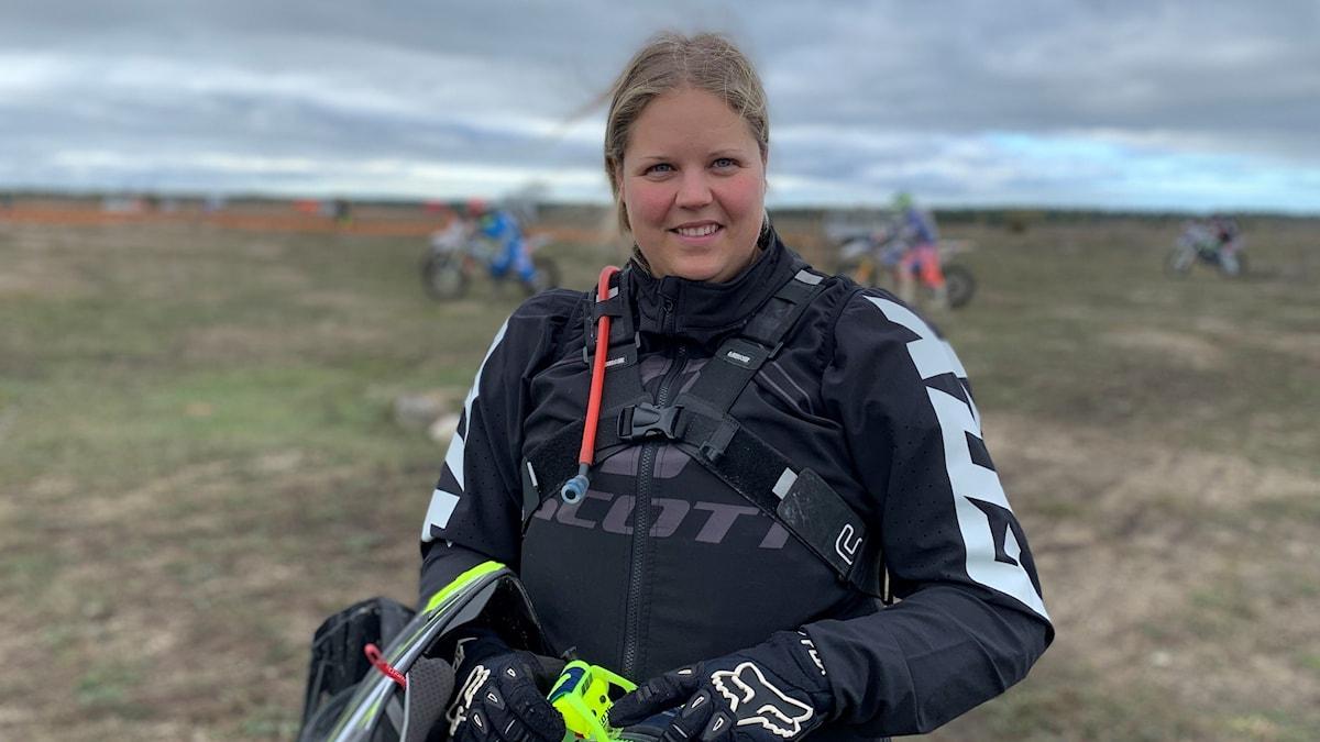 Malin Nygren står på Tofta skjutfält iklädd enduroförarkläder.