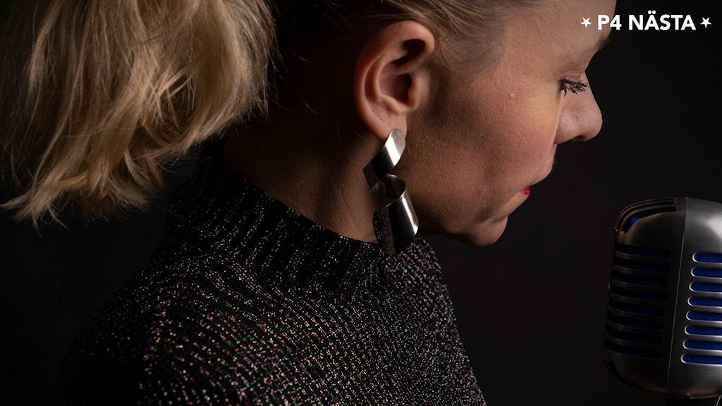 En närbild på en blond kvinna framför en gammaldags mikrofon.