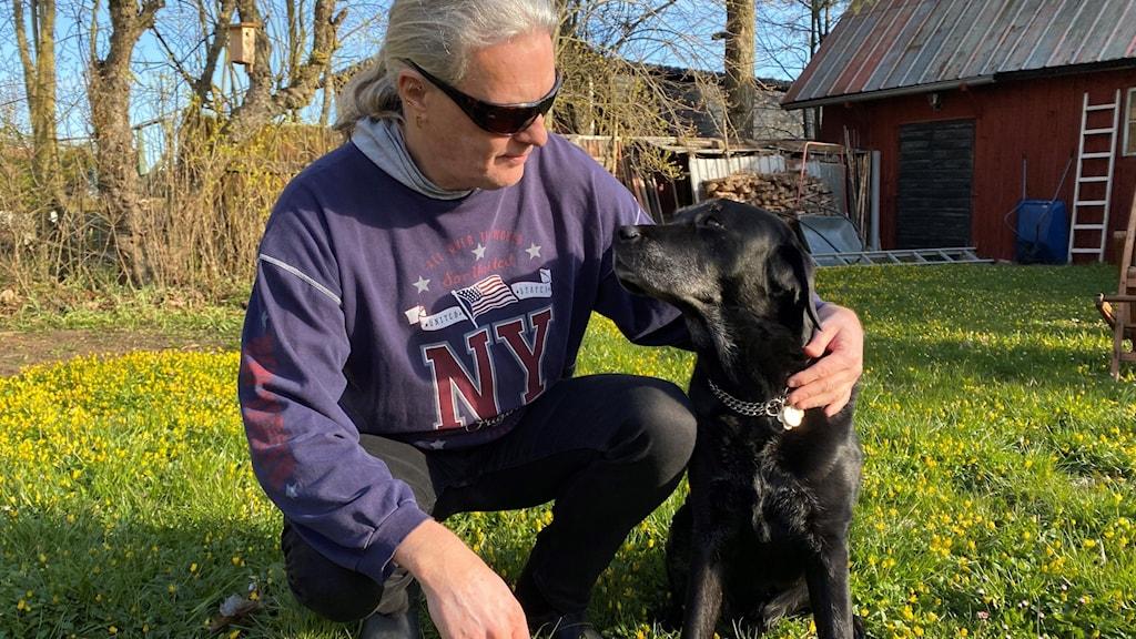 En man sitter på huk på en gräsmatta och håller om en svart labrador.