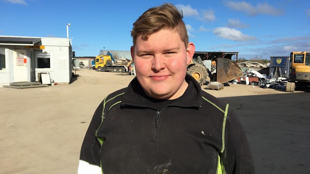 En ung kille i arbetskläder på en återvinningsstation.