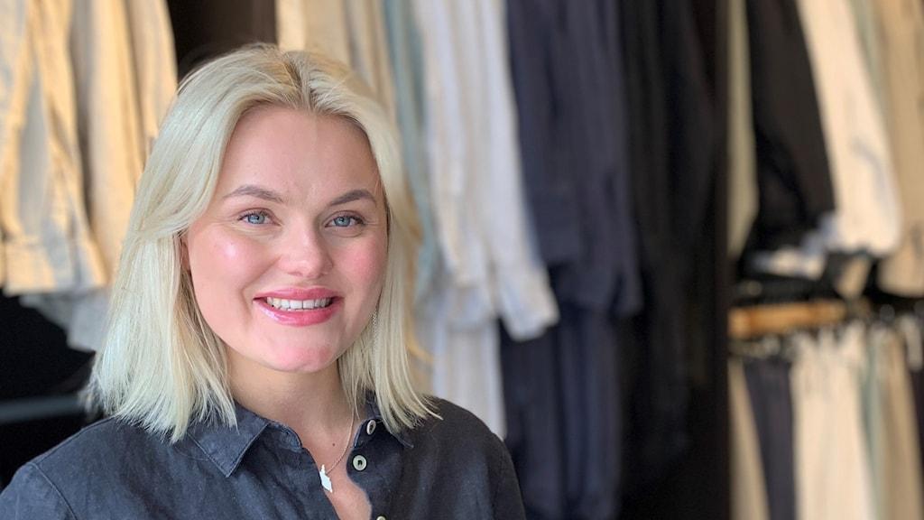 Porträttbild på ung kvinna i blont hår. Hon står i en klädaffär och bakom henne ser man kläder som hänger.