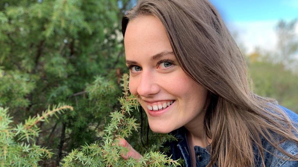 Elisabeth Hellström står utomhus bredvid en buske.