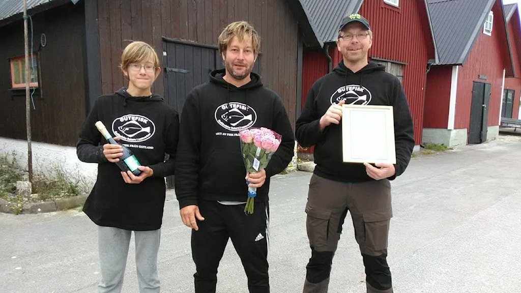 Tre personer står framför fiskebodar med prisplakat, blommor och bubbel.