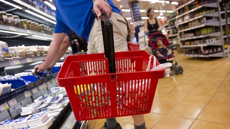 En person i en matvarubutik plockar varor i en korg.