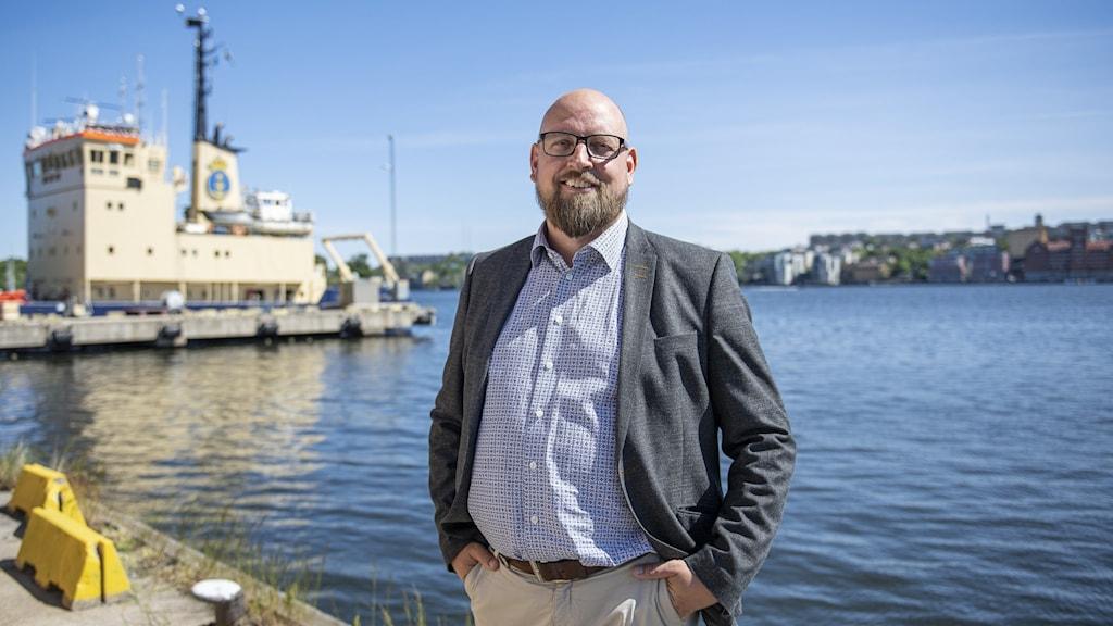 Fredrik Backman, rederidirektör på Sjöfartsverket, ser glad ut och har händerna i byxfickorna. Han står på en kaj med ett fartyg i bakgrunden.