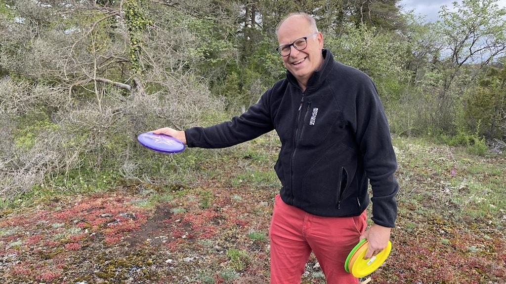 En man i svart jacka och röda byxor håller i flera frisbees och är på väg att kasta en.
