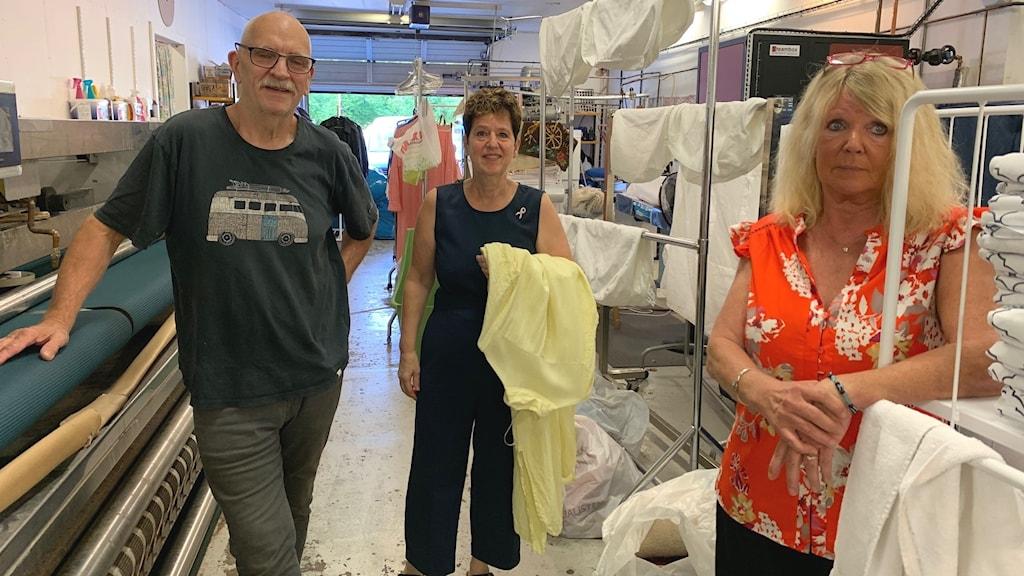 En man och två kvinnor står inne på ett tvätteri.