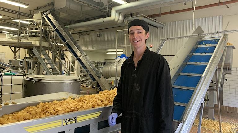 En man står intill ett transportband i en chipsfabrik.