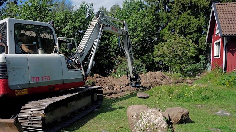 Grävmaskin gräver för kommunalt vatten och avlopp till ett fritidshus