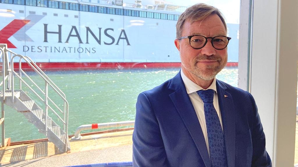 Gotlandsbolagets vd Håkan Johansson står framför ett fönster där Hansa Destinations fartyg syns i bakgrunden.