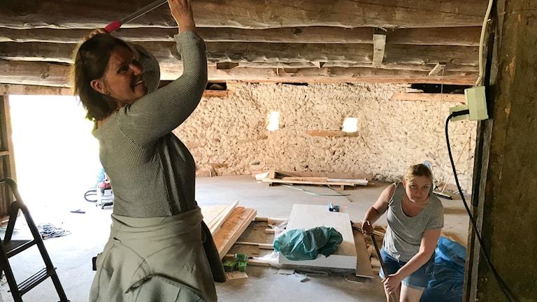 Museicheferna Susanne Thedéen och Jenny Westfält sopar i ladan