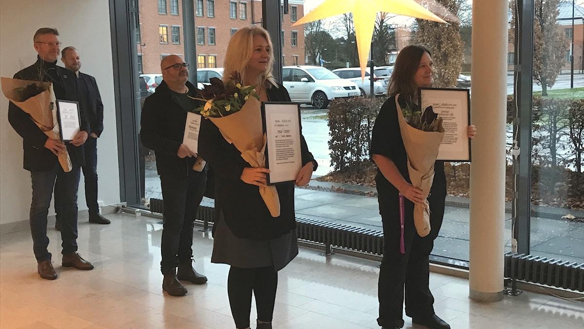 Pristagare med blommor och diplom på rådhuset.