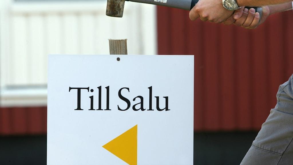 """En hammare bankar ner en skylt med texten """"Till salu""""."""