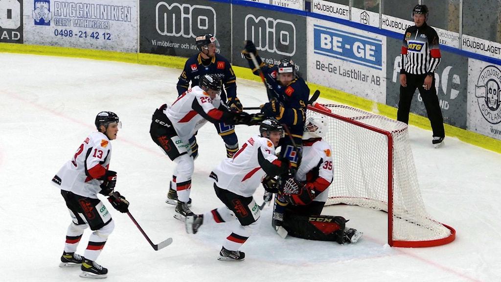 Ishockeyspelare på isen vid målet.