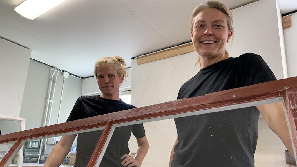Två kvinnor som lagar ett fönster i en verkstad
