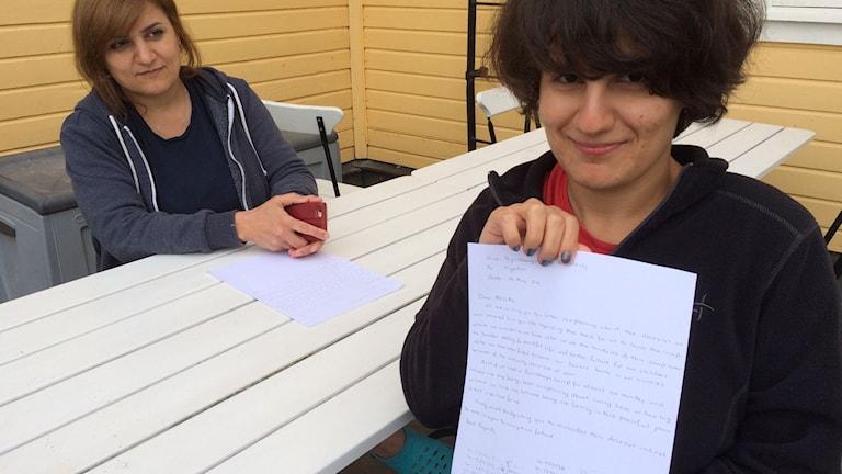 Payman är mamma till Sava (till höger) som håller i en protestlista. Foto: Patrik Annerud/Sveriges Radio