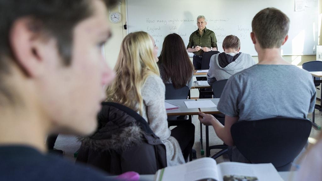 En gymnasieklass med en lärare vid tavlan.