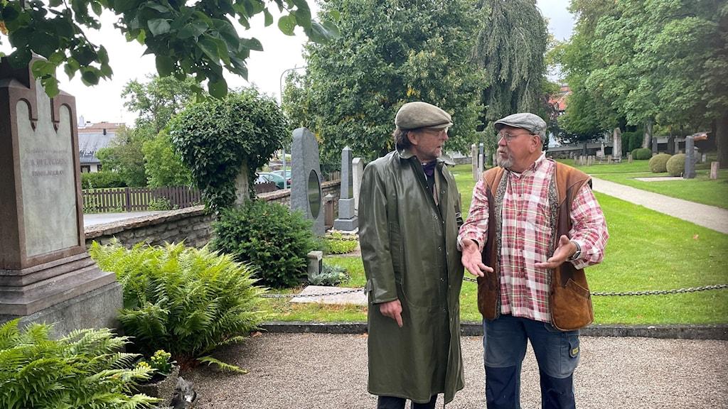 Två män i samspråk vid en grav på Södra kyrkogården.