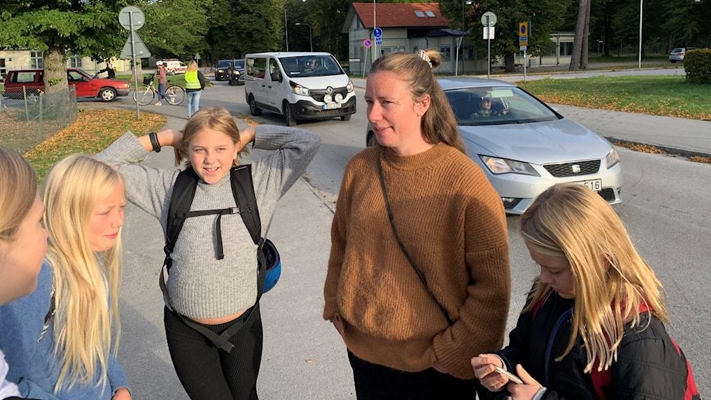 Fyra barn och en vuxen kvinna står på en trottoar vid en bilväg.