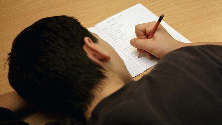tonåring hänger över skolbok