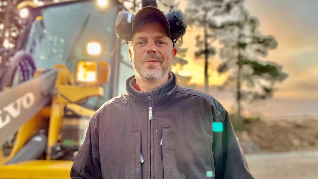 Olof Ahlby står utomhus framför en grävmaskin.