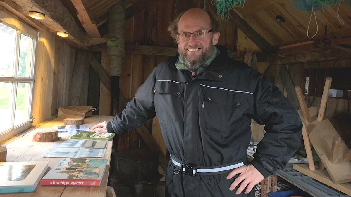En man visar upp sin vykortssamling i en fiskebod