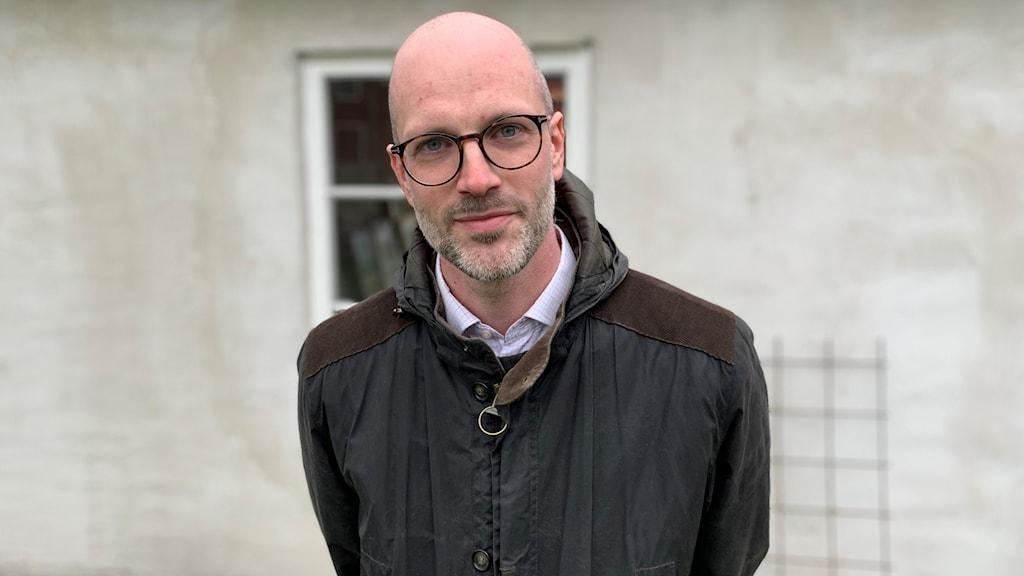 En man i jacka och glasögon står utomhus vid ett stenhus.