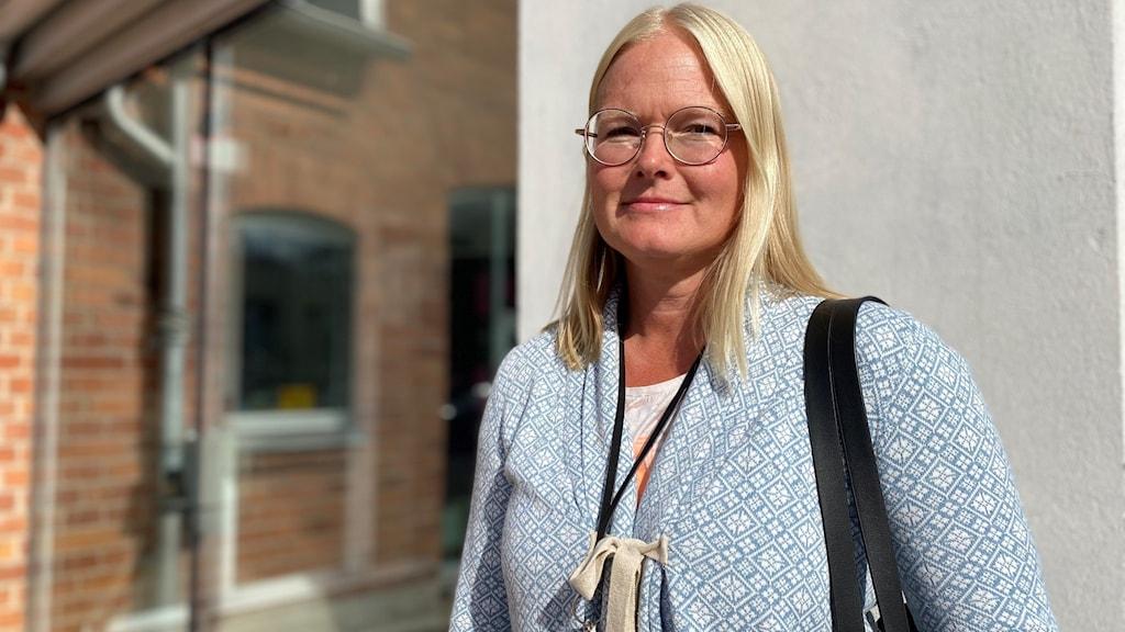 Madelene Johansson står utomhus i en ljusblå kofta. Hon har blont hår och glasögon.