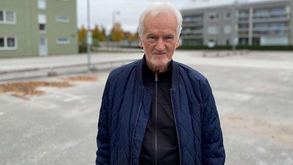 Kjell-Åke Nordström står utomhus på en tom parkeringsplats.